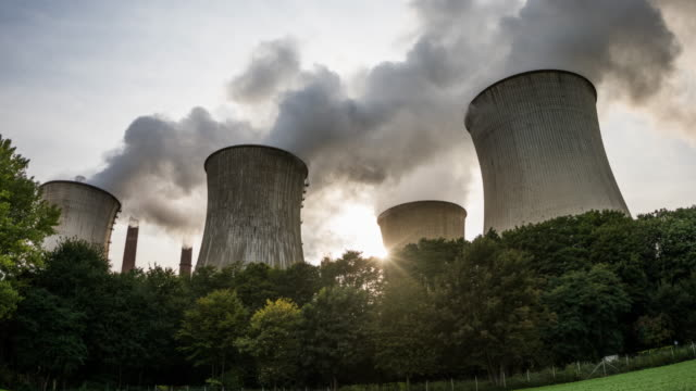 Hyperlapse: Pollution - Cooling Tower of a coal burning power plant. Hyperlapse shot of cooling towers from a coal fired power station. Long distance tracking shot. Steam cloud of industrial plant in dramatic backlight. coal stock videos & royalty-free footage