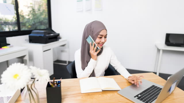 4k hyperlapse time lapse of beautiful asian muslim woman working using laptop in modern office. small business company owner, startup entrepreneur, or working woman lifestyle concept - owner laptop smartphone video stock e b–roll