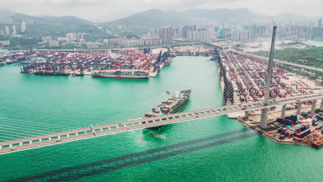 4K UHD hyperlapse timelapse of Stonecutters bridge and Hong Kong port with cargo container ship, crane, and car traffic. Logistic industry or freight transportation business concept, drone aerial view 4K UHD hyperlapse timelapse of Stonecutters bridge and Hong Kong port with cargo container ship, crane, and car traffic. Logistic industry or freight transportation business concept, drone aerial view industrial ship stock videos & royalty-free footage
