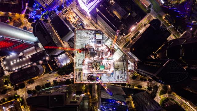 4k 在市區夜間施工現場、起重機和汽車交通的超延時失效。無人機空中視圖。工業企業或土木工程技術概念 - 起重機 個影片檔及 b 捲影像