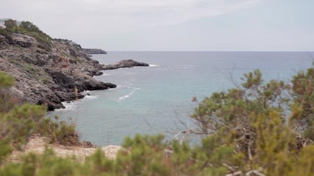 ibiza cliffs, panoramic image of an ibiza cove in summer - formaggio comté video stock e b–roll