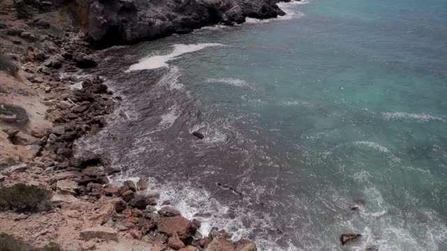 ibiza cliffs, view from ibiza cliff, waves breaking - formaggio comté video stock e b–roll