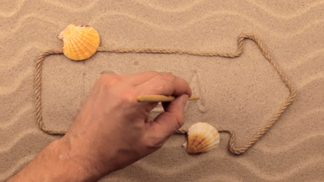 Ibiza inscription written by hand on the sand, in the pointer made from rope. video