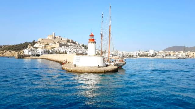vídeos de stock e filmes b-roll de ibiza lighthouse from calm sea at daylight, in summer very popular, sandy coast have a fantastic view of island, ibiza, balearic island - ibiza