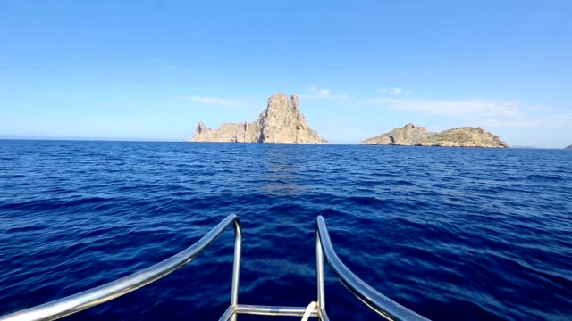 Ibiza yacht reaching Es Vedra island in Mediterranean blue sea video