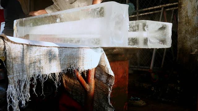 buz göğsünden müşterilerine satmadan önce tutulması için buz blokları - döner lamalı testere stok videoları ve detay görüntü çekimi