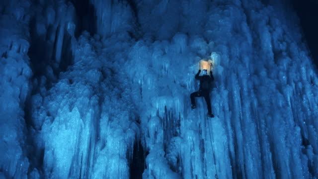 ice climber ascending the slope in wonderful night light - eisklettern stock-videos und b-roll-filmmaterial