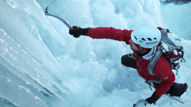 ice climber ascending the slope using two axes - eisklettern stock-videos und b-roll-filmmaterial