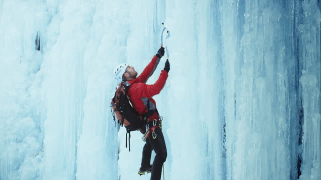 ice climber stepping up the slope - eisklettern stock-videos und b-roll-filmmaterial