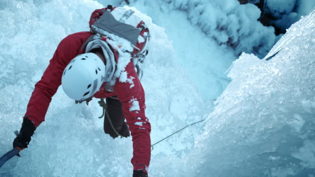 ice climber using the axes to climb up the slope - eisklettern stock-videos und b-roll-filmmaterial