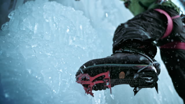 slo mo of ice climber's crampons digging into the ice - eisklettern stock-videos und b-roll-filmmaterial