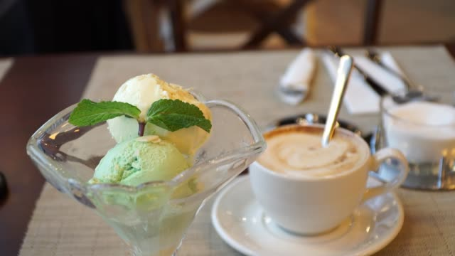 ice cream dessert in a cafe on the background of a cup of cappuccino coffee. vanilla and pistachio ice cream balls with mint leaf - ванильное мороженое стоковые видео и кадры b-roll