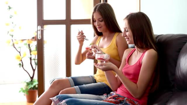 eiscreme für zwei fröhliche mädchen - teenage friends sharing food stock-videos und b-roll-filmmaterial