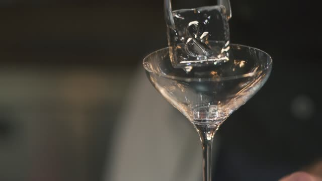 Ice cube falling into a cocktail glass closeup. video