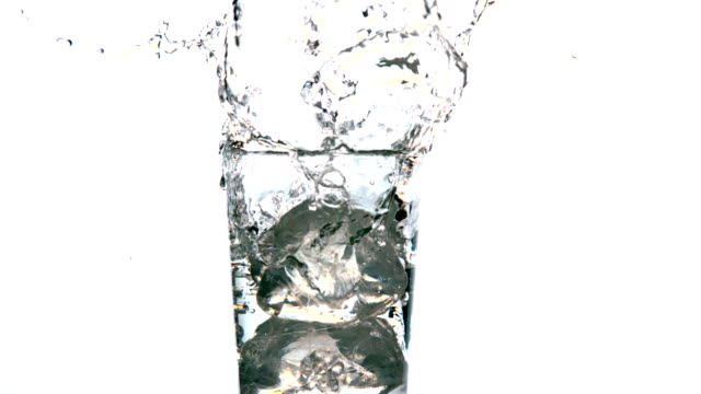 Ice cube falling into glass of water