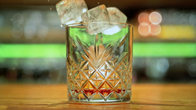 SLO MO DS Ice cubes falling into a glass with liquor Slow motion medium dolly shot of ice cubes falling into a glass with golden-brown liquor. Shot in Slovenia. dolly shot stock videos & royalty-free footage