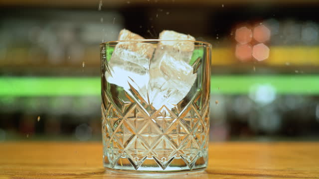 SLO MO DS Ice cubes falling into a rocks glass Slow motion medium dolly shot of ice cubes falling into a decorative rocks glass. Shot in Slovenia. dolly shot stock videos & royalty-free footage