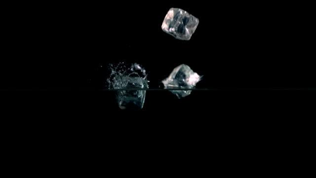 ice cubes falling into water - küp buz stok videoları ve detay görüntü çekimi