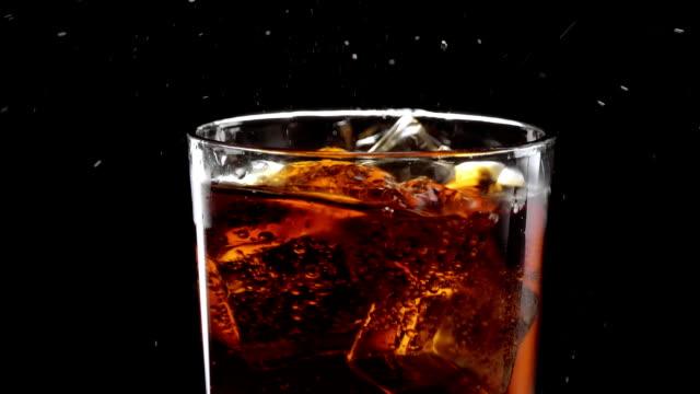 Flotteur de cubes de glace dans un verre de cola de rafraîchissement - Vidéo
