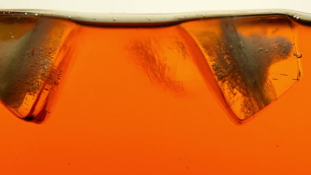 Ice cubes melt in tea or whiskey close up video