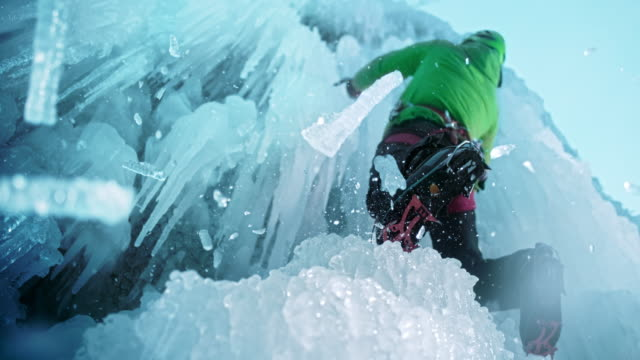 slo mo ice falling as climber uses the axe - eisklettern stock-videos und b-roll-filmmaterial