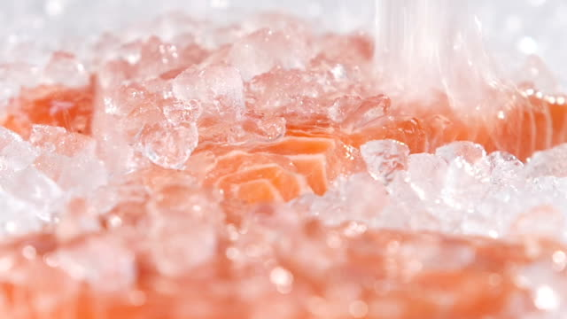 Ice falls on the red fish. Slow motion video
