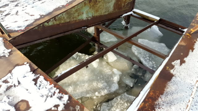 Ice floating on river in spring time under old pier. video