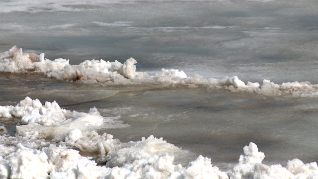 ice floes float on the river in the spring during the ice drift - ghiaccio galleggiante video stock e b–roll
