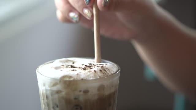 eis hojicha latte und nahaufnahme frau hand - zucker stock-videos und b-roll-filmmaterial