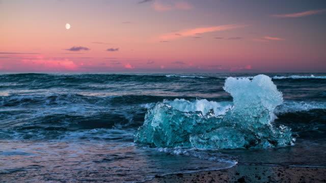 ghiaccio su ghiaccio con acqua onda in spiaggia di jokulsarlon, islanda - ghiaccio galleggiante video stock e b–roll
