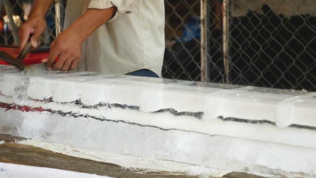 buz blokları kesme ve bir kanca (portre) kullanarak hareketli buz satıcı - döner lamalı testere stok videoları ve detay görüntü çekimi