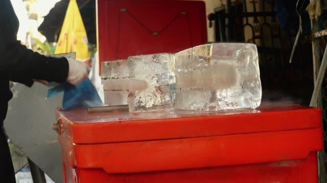 buz satıcı buz onun balta ile küçük blok kesme - döner lamalı testere stok videoları ve detay görüntü çekimi