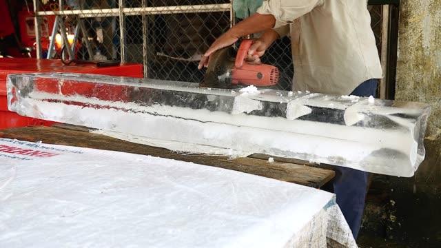 küçük blok buz dışında daha büyük bir daire testere ile ön kesim buz satıcı - döner lamalı testere stok videoları ve detay görüntü çekimi