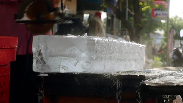 küçük bir daire testere ile buz bloklarını ön kesim buz satıcı - döner lamalı testere stok videoları ve detay görüntü çekimi