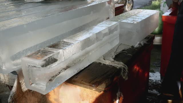 önceden kesilmiş küçük buz blokları bir kanca (portre) kullanarak bir dondurucuya koyarak buz satıcı - döner lamalı testere stok videoları ve detay görüntü çekimi