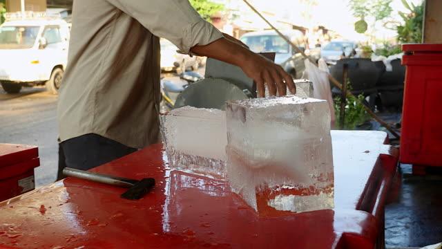 buz satıcı onun balta ile buz blokları bölme - döner lamalı testere stok videoları ve detay görüntü çekimi