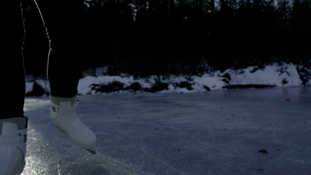 SLOW MOTION CLOSE-UP: Ice skating on frozen lake in forest video