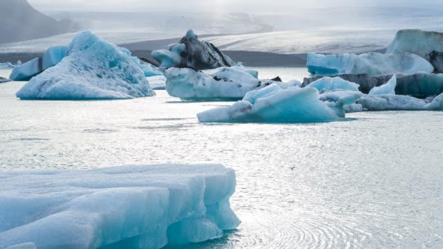 Icebergs at glacier lagoon Beautiful icebergs at Jokulsarlon glacial lagoon in Iceland with Vatnajokull ice cap in the background icecap stock videos & royalty-free footage