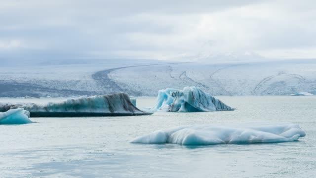 iceberg si sono allontanati dal ghiacciaio vatnajokull, galleggiando nella laguna di jokulsarlon in islanda - ghiaccio galleggiante video stock e b–roll