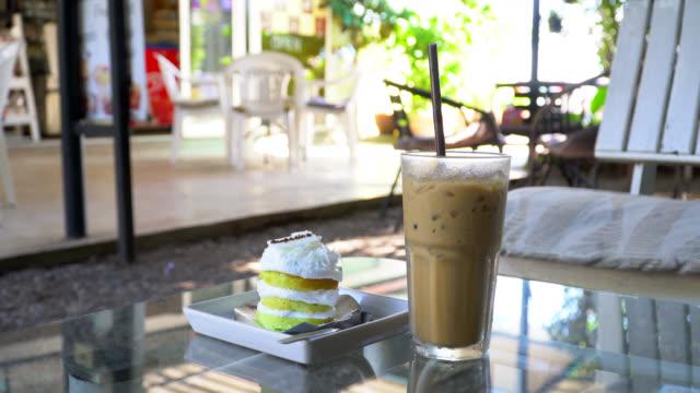 vídeos de stock e filmes b-roll de iced coffee and cake in cafe - café gelado