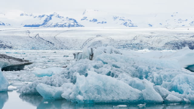 Iceland's glacial lake with icebergs floating in water Iceland's glacial lake Jokulsarlon with icebergs floating in water, Vatnajokull ice cap in the background. Shot in 4K resolution polar climate stock videos & royalty-free footage
