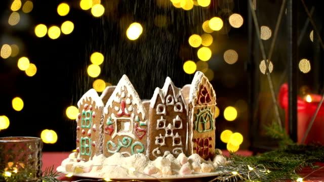 florsocker faller på en jul pepparkakshus som snöfall. - pepparkaka bildbanksvideor och videomaterial från bakom kulisserna