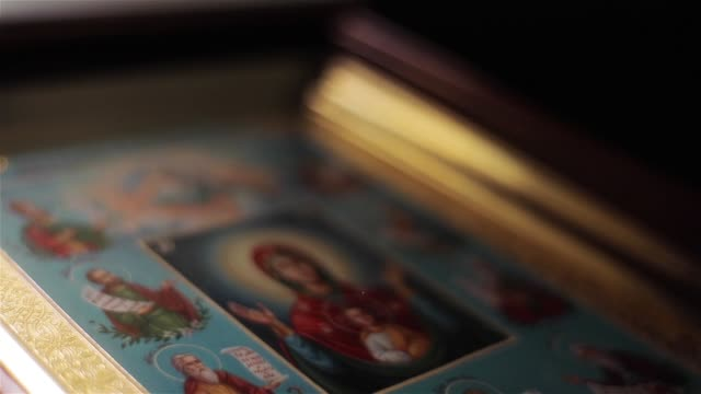 Icon image of Virgin Mary in St Nicholas Orthodox Cathedral in Nice France macro close up light moving. Framed painting of Mother of God in Orans position with Child Jesus attended by saints video