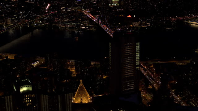 AERIAL: Iconic Brooklyn and Manhattan bridge above the East River lit at night AERIAL HELI SHOT, NO VISIBLE TRADEMARKS: Automobile traffic moving across the iconic Brooklyn and Manhattan bridge lit up with lights on magical summer night in New York City. People traveling to work manhattan bridge stock videos & royalty-free footage