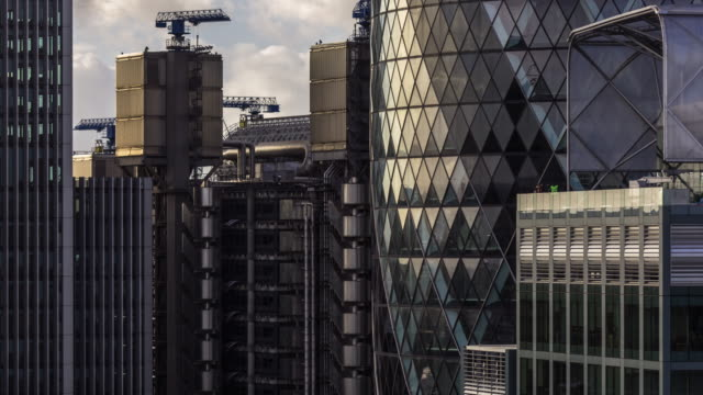 Iconic London Office Buildings - Time Lapse Time lapse showing iconic buildings of the City of London, including the Gherkin and the Lloyds Building. Movement is provided by passing clouds and construction workers on a roof. london architecture stock videos & royalty-free footage