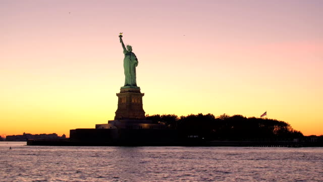 LOW ANGLE: Iconic Statue of Liberty against gorgeous fiery orange sunset sky video
