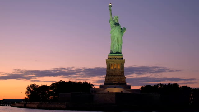 CLOSE UP Iconic Statue of Liberty lit up with lights against fiery sky at sunset video