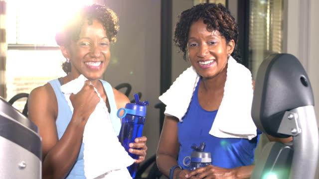 identiska tvilling systrar på gymmet, efter träning - black woman towel workout bildbanksvideor och videomaterial från bakom kulisserna