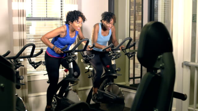 Identical twin sisters exercising at gym on bikes Two mature African-American women in their 40s, identical twin sisters, exercising at the gym. They are cycling on exercise or exercising bikes, side by side, talking and smiling. sister stock videos & royalty-free footage