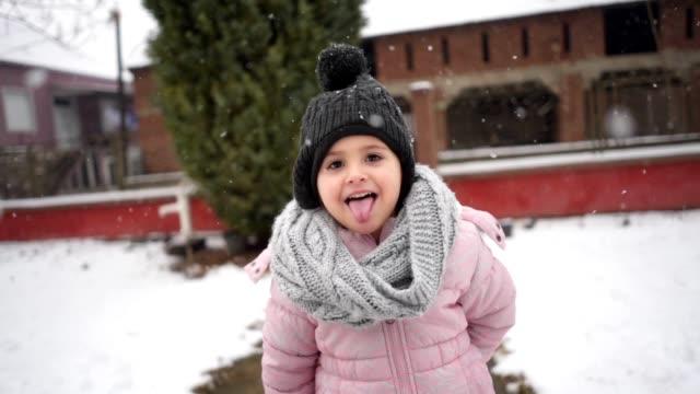 dört yaşındaki bir kız zevk kar idlyllic sahne düşmek - kep şapka stok videoları ve detay görüntü çekimi